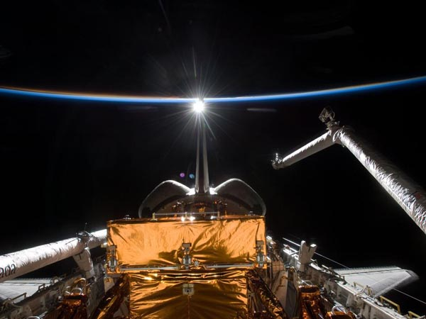 Backdropped by the blackness of space and the thin line of Earth's atmosphere, space shuttle Atlantis' payload bay, Canadian-built remote manipulator system robotic arm, vertical stabilizer and orbital maneuvering system pods are featured in this image photographed by the STS-125 crew on flight day 10. (http://www.nasa.gov)