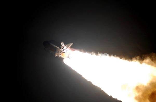 In this stunning picture following the launch, the glare from Endeavour's three main rocket engines and flanking solid fuel booster rockets illuminates the orbiter's tail section and the large, orange external fuel tank. (http://apod.nasa.gov)